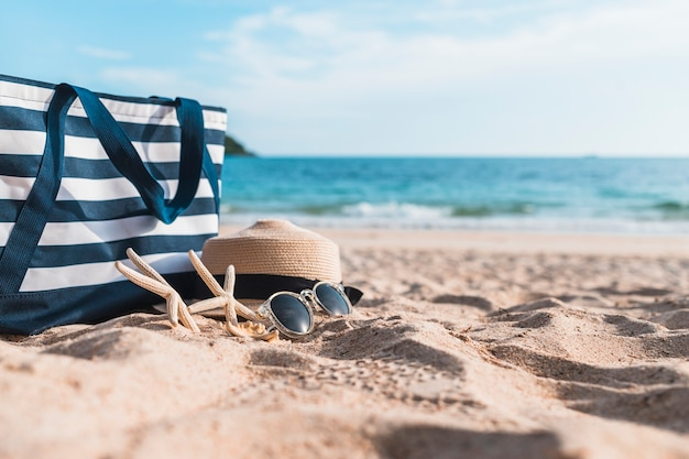 Drie zeesterren met blauwe zak op zand