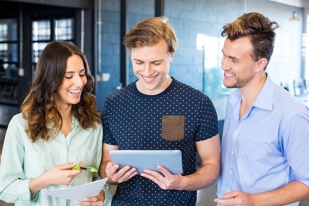 Drie zekere collega's die in bureau met documenten en tablet bespreken