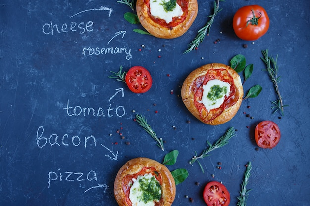 Drie zelfgemaakte mini-pizza met tomaten, kaas en spek, verwondingen en kruiden.