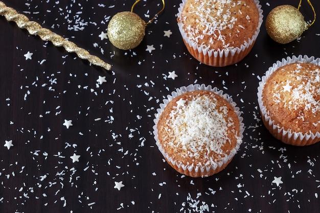 Drie zelfgemaakte muffins versieren kokospoeder op donker hout