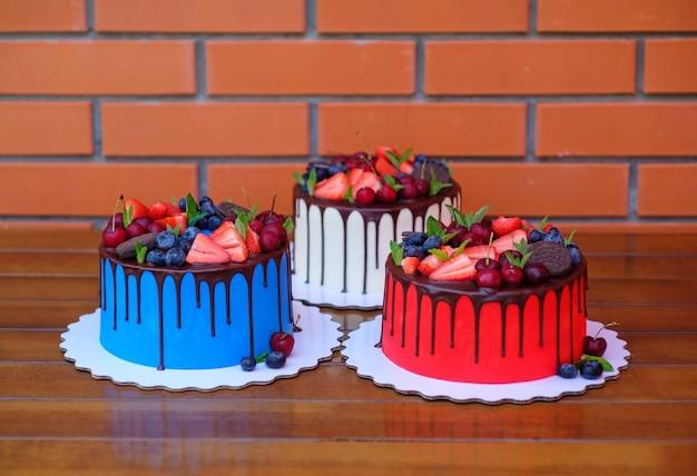 Drie zelfgemaakte taarten met witte, blauwe, rode kaascrème en chocoladesuikerglazuur, versierd met kersen, aardbeien en bosbessen, op een houten tafel tegen een bakstenen muur