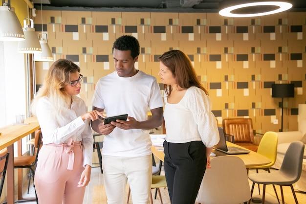 Drie zelfverzekerde ontwerpers staan samen en praten