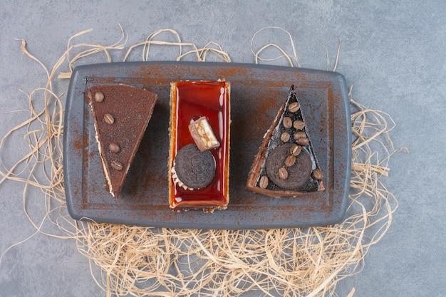 Drie zoet vers stuk taarten op snijplank.