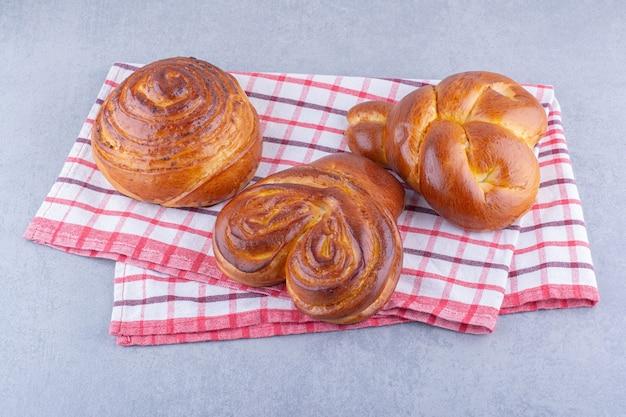 Drie zoete broodjes gerangschikt op een handdoek op een marmeren oppervlak