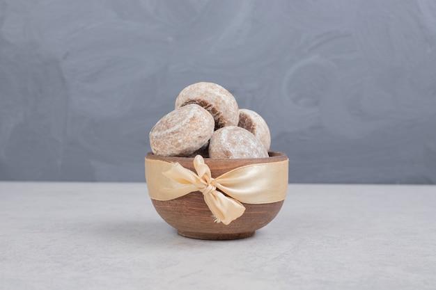 Drie zoete koekjes met gouden boog op houten kom