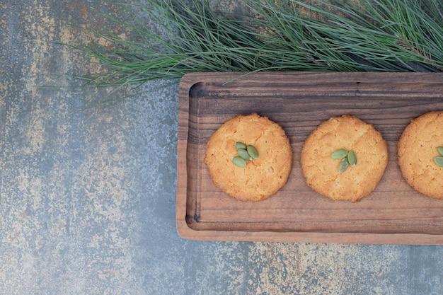 Drie zoete koekjes met pompoenpitten op een houten bord.