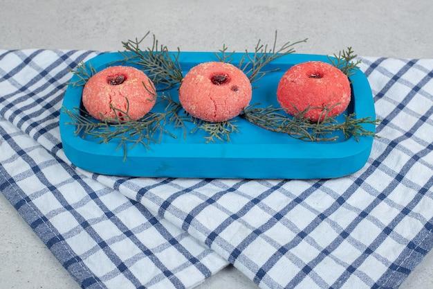 Drie zoete roze ronde koekjes op blauw bord.