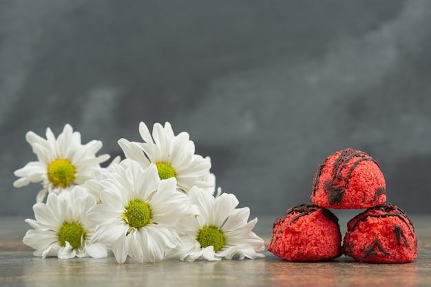 Drie zoete snoepjes met boeket bloemen op marmeren tafel.