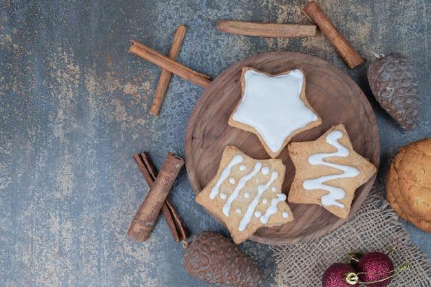 Drie zoete sterren van kerstmiskoekjes op houten plaat met rode ballen, dennenappel en pijpjes kaneel.
