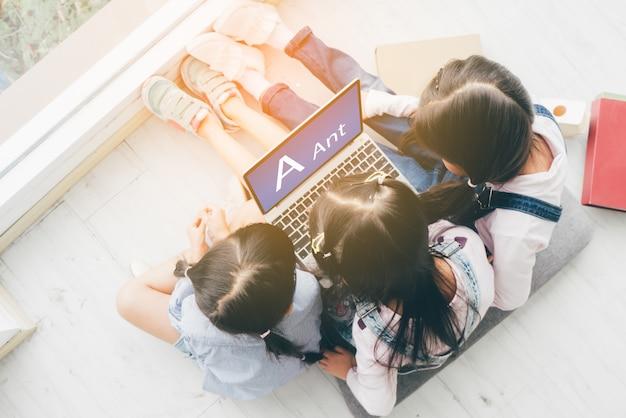 Drie zusters, liggen op de vloer en gebruiken een laptop om hun schoolwerk te doen.
