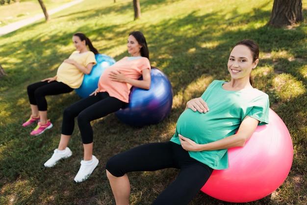 Drie zwangere vrouwen liggen op yogaballen in het park