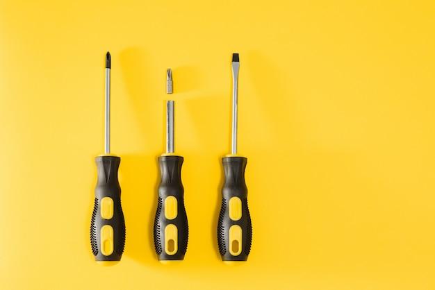 Drie zwarte en gele schroevendraaiers op een gele achtergrond met ruimte voor tekst. gereedschap, constructie en werkplaats, huisreparatie, slusarwerkzaamheden.