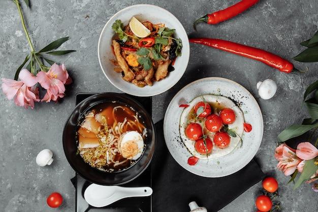 Driegangen zakenlunch. cherrytomaatjes met tofumousse, thaise rijst met kip en groenten, aziatische noedelsoep, ramen met kip.
