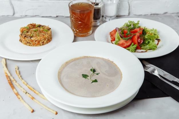 Driegangenstel op een tafel in een restaurant, cafémenu. zakenlunch van een bord met champignonroomsoep, met kip en ei, een salade van verse groenten en pilaf.