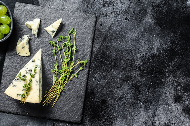 Driehoek van blauwe kaas met druiven op snijplank. zwarte achtergrond. bovenaanzicht. kopieer ruimte