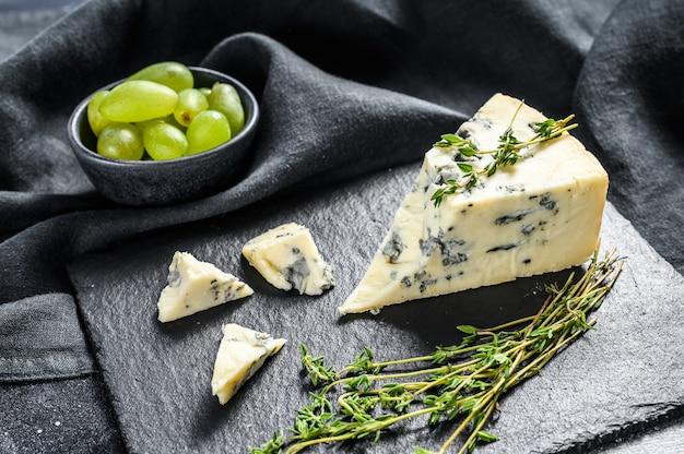 Driehoek van blauwe kaas met druiven op snijplank. zwarte achtergrond. bovenaanzicht