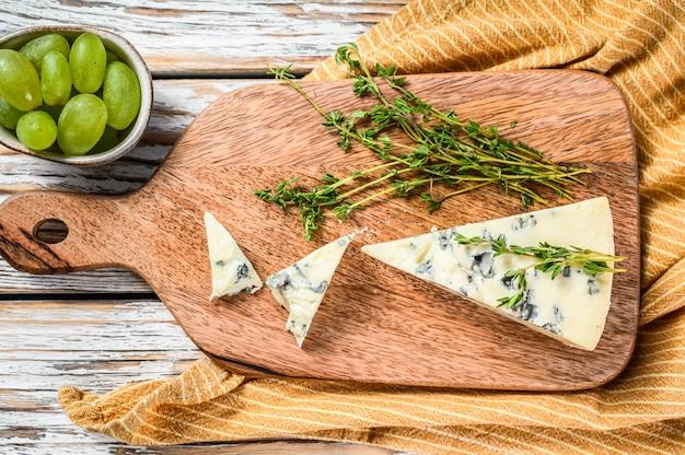 Driehoek van blauwe kaas met druiven. witte houten achtergrond. bovenaanzicht. kopieer ruimte