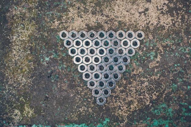 Driehoek van metalen moeren op beton