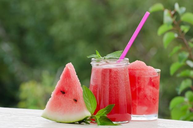 Driehoek van watermeloen smoothie met ijs en een takje munt