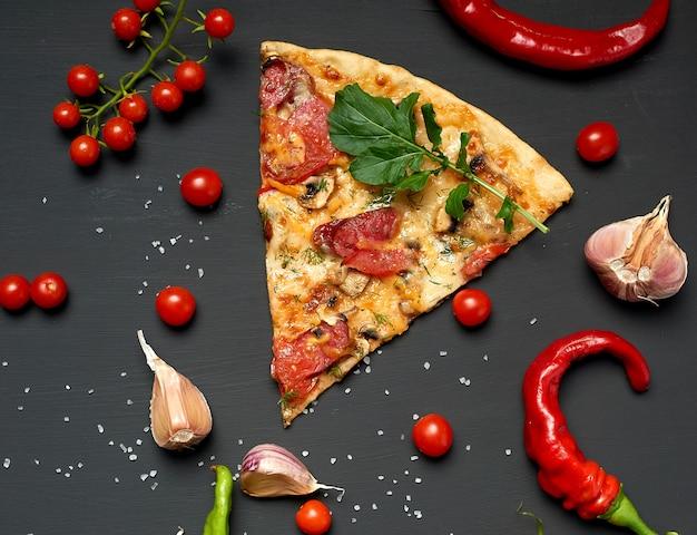 Driehoekig stuk gebakken pizza met champignons, gerookte worstjes, tomaten en kaas