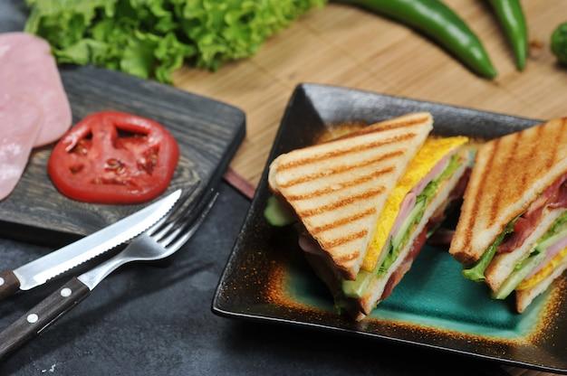 Driehoekige broodjes met ham en omelet op een bord