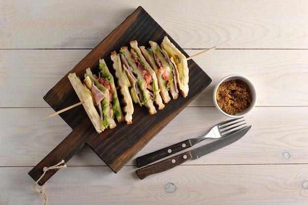 Driehoekige broodjes met ham geregen op houten spiesjes