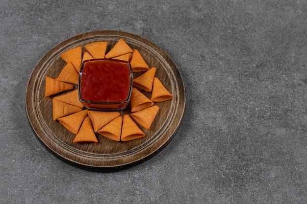 Driehoekige chips en ketchup op een houten bord.