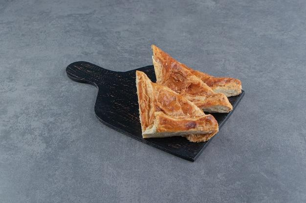 Driehoekige gebakjes gevuld met kaas op een houten bord.