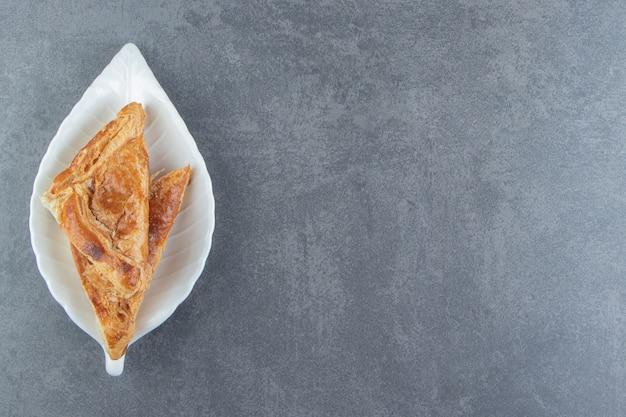 Driehoekige gebakjes gevuld met kaas op witte plaat.