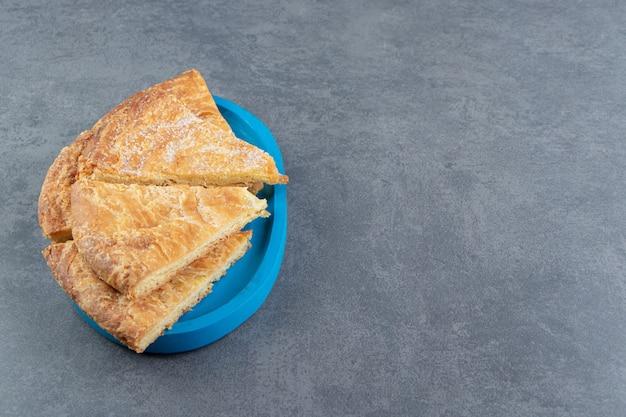Driehoekige gebakjes op blauw bord.