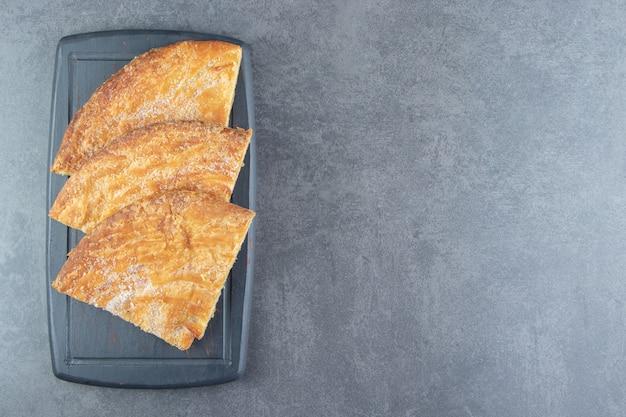 Driehoekige gebakjes op donker bord.