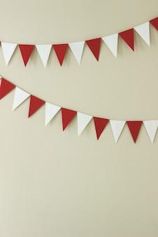 Driehoekige papieren handgemaakte slingers van wit en rood op een lichte muur.