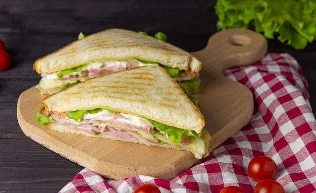 Driehoekige sandwiches met toast, sla en groenten op een donkere achtergrond. gezond en lekker ontbijt of lunch.