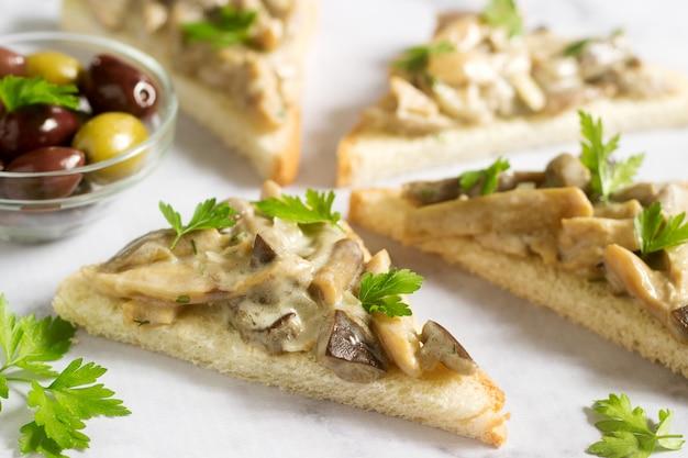 Driehoekige sandwiches met zomerchampignons bereid met room en kruiden geserveerd met olijven.