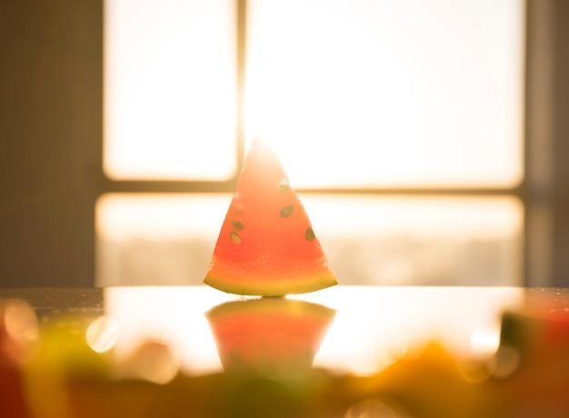 Driehoekige vorm van watermeloen met zaden op reflecterend bureau in fel zonlicht