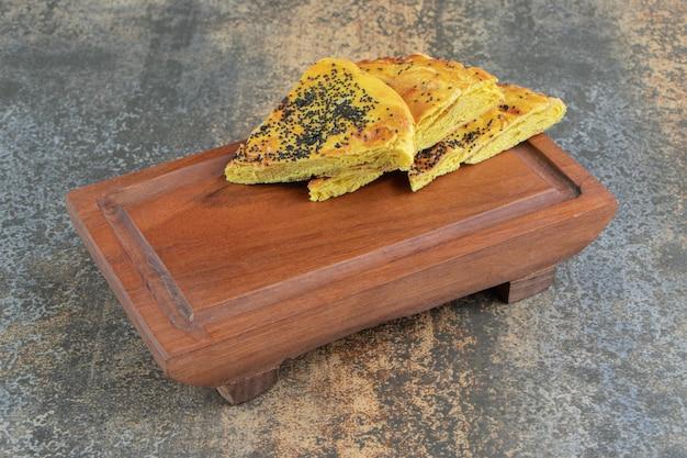 Driehoeksgebak met maanzaad op een houten bord