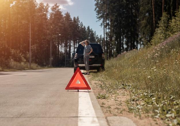 Driehoekswaarschuwingsbord aan de kant van de weg na autopech en droevige vrouwelijke bestuurder die wacht op noodgeval