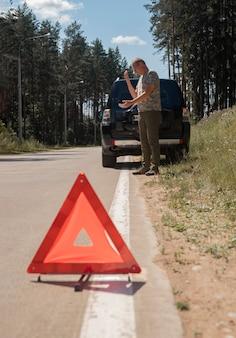 Driehoekswaarschuwingsbord op de weg na autopech en chauffeur die telefonisch wacht op noodgevallen