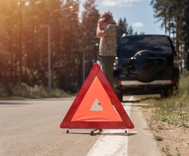 Driehoekswaarschuwingsbord op weg na autoonderbreking en bestuurder die op mobiele telefoon spreekt die roept om opstaan...