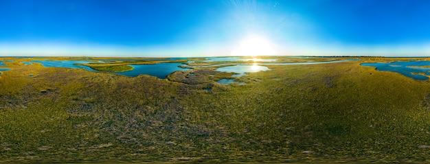 Driehonderdzestig graden panorama van blauwe lucht en een complex van meren omgeven door groen struikgewas op een zonnige zomerdag