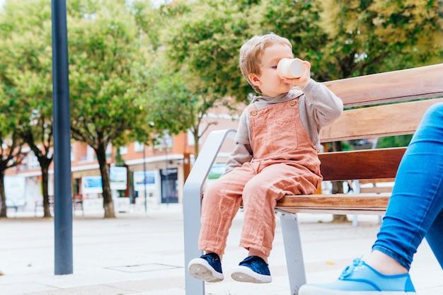 Driejarige jongen die een bak ijs snijdt met zijn mond op straat met zijn moeder
