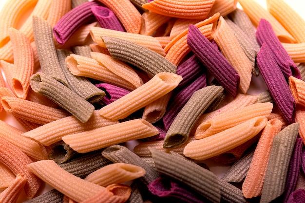 Driekleurige penne pasta. tomaten, spinazie en tarwepasta's. veelkleurige pasta van rode, gele en groene kleur, biologische vierkante achtergrond.