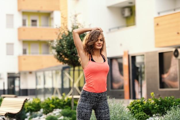 Driekwart lengte van charmante fit blanke vrouw in sportkleding