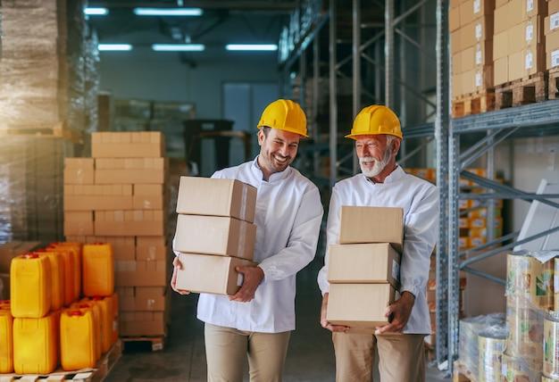 Driekwart lengte van twee lachende blanke opslagmedewerkers in witte uniformen en met gele helmen met dozen in opslag.