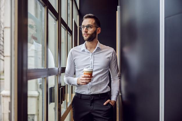 Driekwart lengte van zakenman permanent binnen, wegwerp beker met koffie te houden en trog glas te kijken.