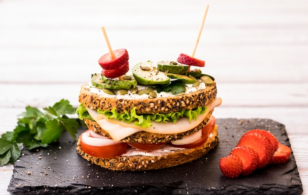 Drielaags broodje met diverse groenten, kalkoenvlees en avocado in een volkorenbrood met pitjes. rode aardbei. gezond dieetconcept.