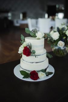 Drieledige bruidstaart versierd met verse bloemen modetaart