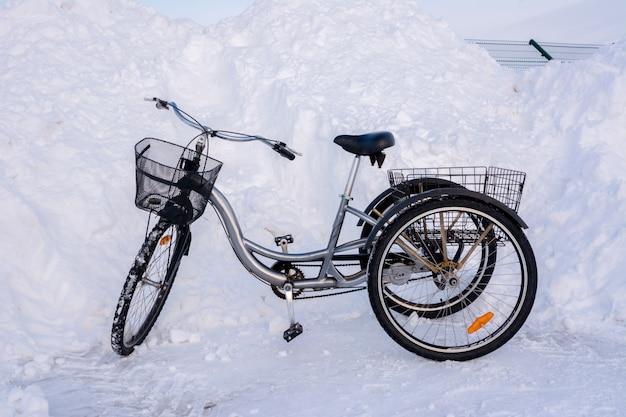 Driewielige fiets in de winter op een achtergrond van besneeuwde heuvels, sneeuwbanken, hekken en asfalt.
