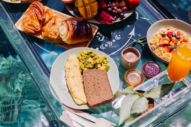 Drijvend ontbijt in een geweldige hotelvilla in een blauw zwembad