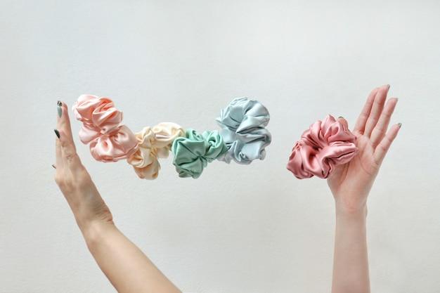 Drijvende kleurrijke zijden scrunchies op de hand vliegende of vallende haarband van de vrouw voor kopieerruimte voor meisjes